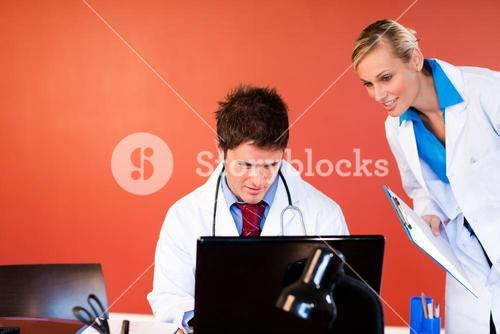 Doctors working with a laptop in office