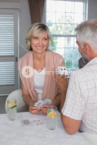 Smiling woman playing cards with man
