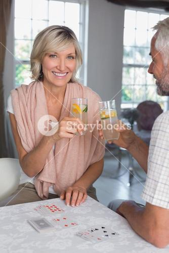 Mature couple toasting drinks while playing cards