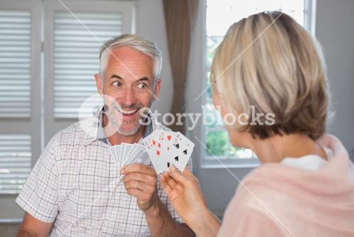 Happy mature man playing cards with woman at home