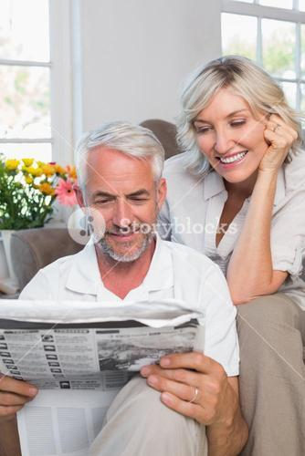 Mature couple reading newspaper