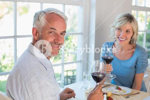 Portrait of a mature couple with wine glasses having food