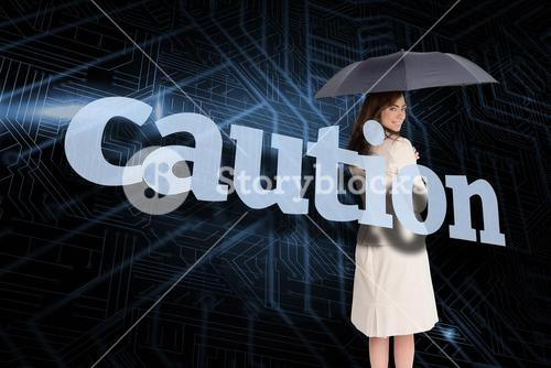 Businesswoman holding umbrella behind the word caution