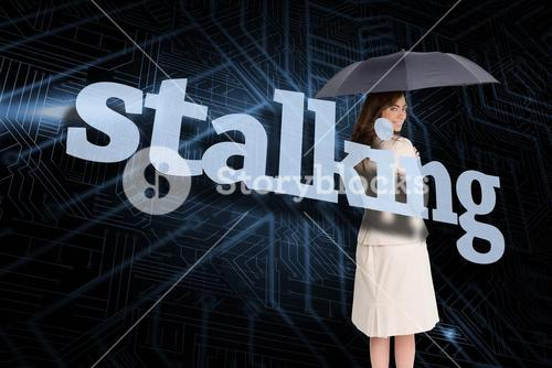 Businesswoman holding umbrella behind the word stalking