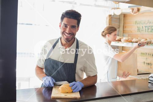 Smiling waiter at the coffee shop counter