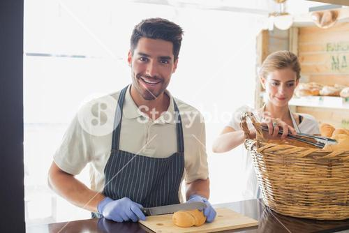 Smiling waiter with croissant at the coffee shop counter