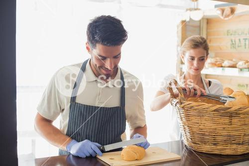 Young waiter with croissant at the coffee shop counter
