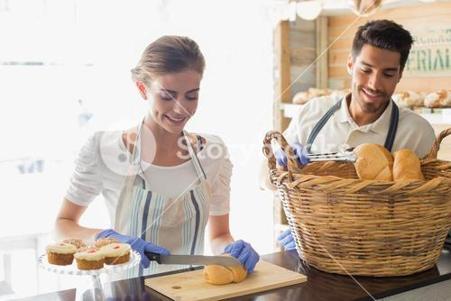 Smiling people with croissants at coffee shop counter