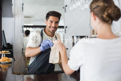 Waiter giving packed food to a woman at coffee shop
