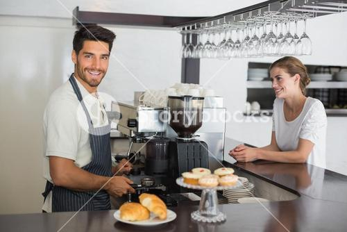 Male cafe owner with woman at the coffee shop