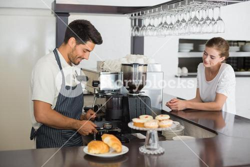 Male cafe owner with woman at coffee shop