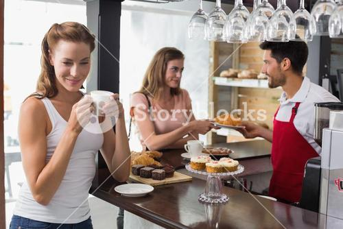 Woman drinking coffee with friend and barista in coffee shop