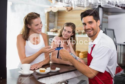 Friends paying bill at coffee shop using card bill