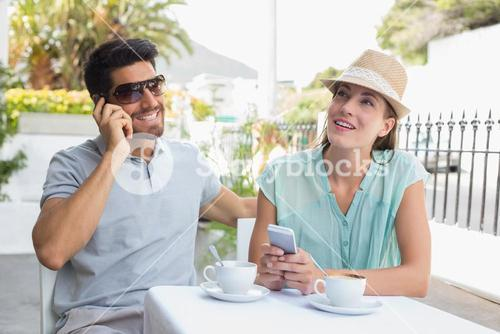 Couple with mobile phones at coffee shop