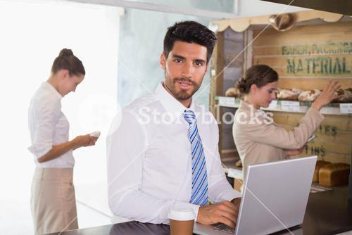 Businessman using laptop in office cafeteria
