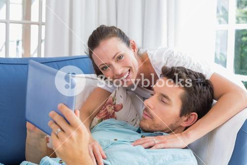 Loving couple reading book on couch