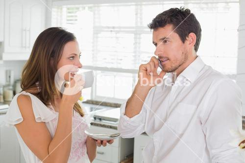 Woman drinking coffee while man using cellphone
