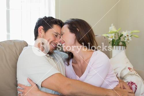 Cheerful loving couple on couch at home