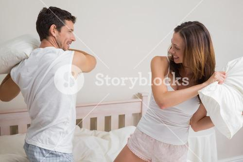 Cheerful couple pillow fighting in bed