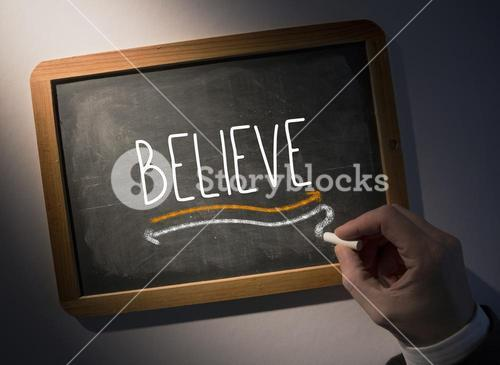 Hand writing Believe on chalkboard