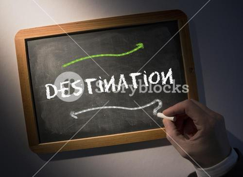 Hand writing Destination on chalkboard