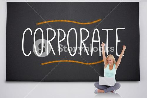 Cheering blonde with laptop against the word corporate