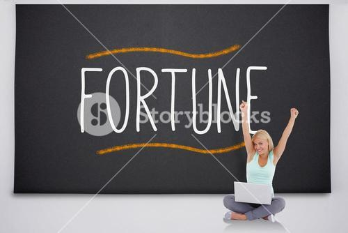 Cheering blonde with laptop against the word fortune