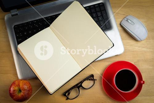 Overhead of laptop with notebook