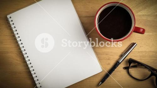 Overhead of notepad and pen and coffee