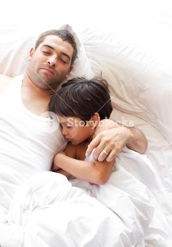 Portrait of a father and his son looking at the camera on the bed