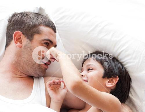 Joyful father and his son looking at the camera on the bed