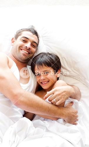 Charming father and his son looking at the camera on the bed