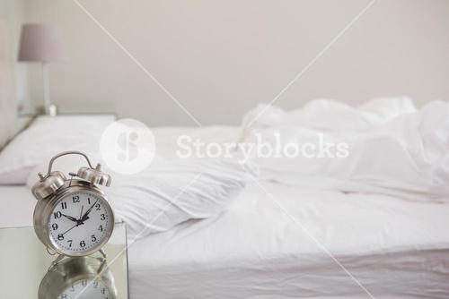 Messy bed with alarm clock on bedside table