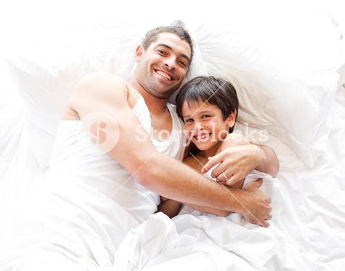 Happy father and his son looking at the camera on the bed