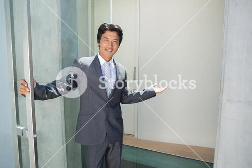 Confident estate agent standing at front door welcoming you in