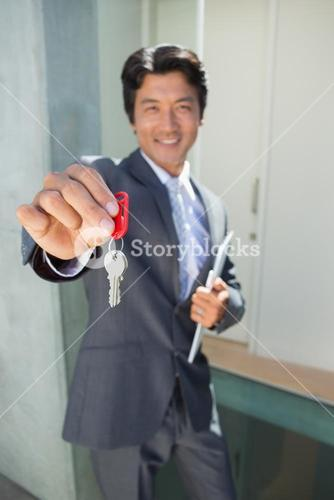 Confident estate agent standing at front door showing key