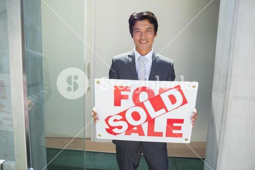 Confident estate agent standing at front door showing sold sign