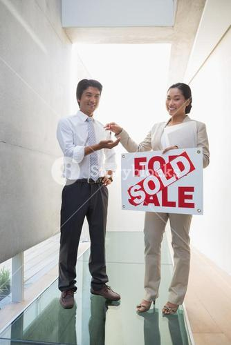 Estate agent giving keys to new home owner