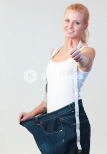Portrait of a woman with thumb up wearing big jeans focus on thumb