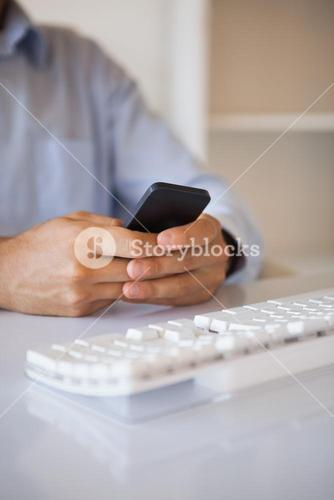 Businessman texting on phone at desk
