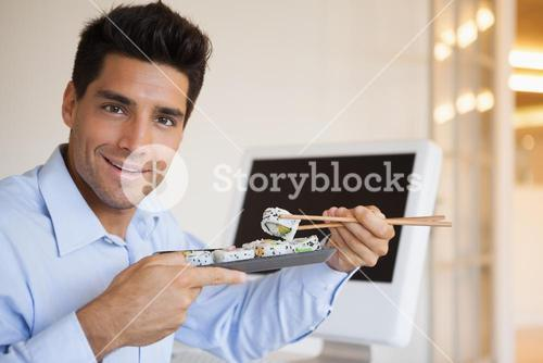 Casual businessman enjoying sushi at his desk