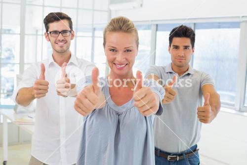 Casual business team smiling at camera with thumbs up