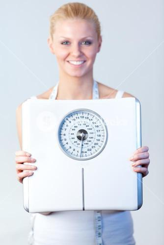 Smiling woman holding a scales with focus on scales