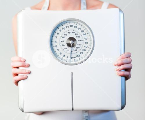 Close up of a woman holding a scales with focus on scales