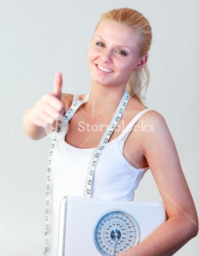 Attractive woman with thumb up holding a scales focus on woman