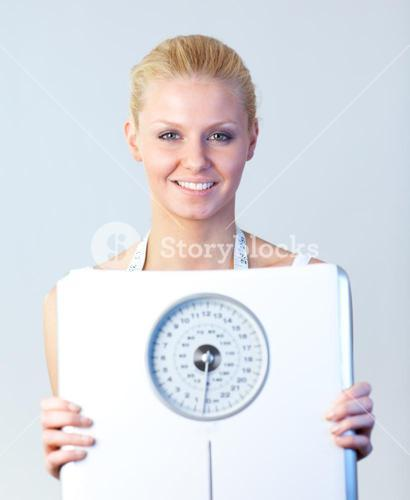Friendly woman holding a scales focus on woman
