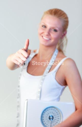 Beautiful woman with thumb up holding a scales focus on thumb