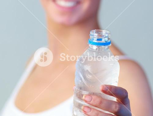 Close up of a woman with a bottle of water with focus on water