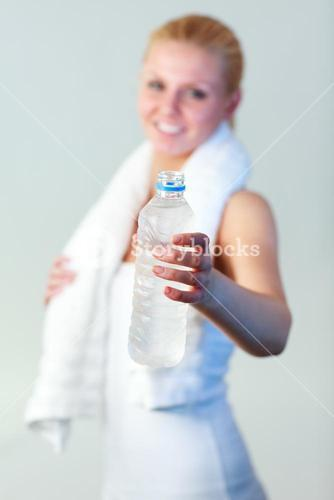 Smiling woman with a bottle of water and a towel with focus on water