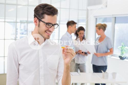 Casual businessman smiling at his electronic cigarette